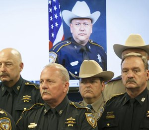 In this Saturday, Aug. 29, 2015 file photo, law enforcement officers attend a news conference in Houston on the shooting death of Harris County Sheriff's Deputy Darren Goforth, pictured in the background. (AP Image)