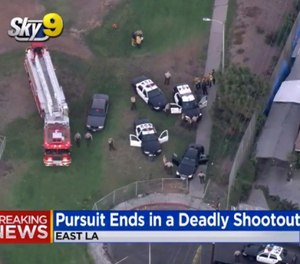 This still image taken from video provided by CBS2/KCAL9 shows the scene of gunfight at an East Los Angeles park that has wounded two Los Angeles County sheriff's deputies and left a suspect dead, Wednesday, Sept. 19, 2018. (CBS2/KCAL9 via AP)