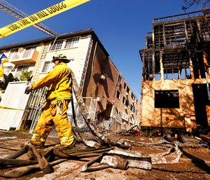 LA City Firefighter Jose Carreon hauling hoses on mop up at the scene. (Al Seib/Los Angeles Times via AP)