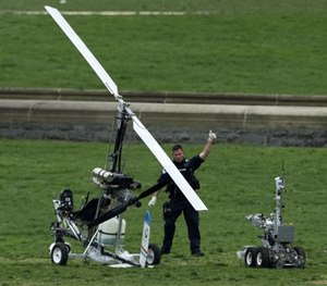 A Capitol Police officer flashes a thumbs up after inspecting the small helicopter a man landed on the West Lawn of the Capitol in Washington. (AP Image)