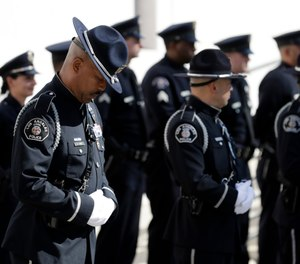 An police officer lowers his head as he waits for the procession for Ventura County Sheriff's Sgt. Ron Helus at the Calvary Community Church Thursday, Nov. 15, 2018, in Westlake Village, Calif. (AP Photo/Marcio Jose Sanchez, Pool)