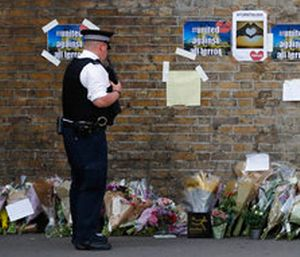 A police officer stands near floral tributes in Finsbury Park after an incident where a van struck pedestrians. (AP Photo/Frank Augstein)