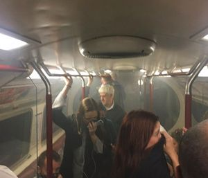 Commuters cover their mouths as smoke fills the carriage of a Bakerloo line train. (Joe Bunting via AP)