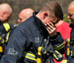 A firefighter puts his hand to his face as he looks at the floral tributes before a minute's silence near to Grenfell Tower. (Dominic Lipinski/PA via AP)