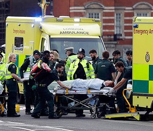 Emergency services transport an injured person to an ambulance, close to the Houses of Parliament in London, Wednesday, March 22, 2017. (AP Photo/Matt Dunham)