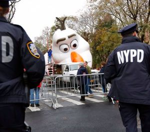 """Police officers stand near the site where a large balloon of Olaf, from the animated film, """"Frozen"""", is being inflated for the Thanksgiving Day parade in New York, Wednesday, Nov. 22, 2017. (AP Photo/Seth Wenig)"""