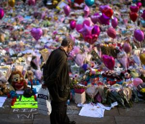 A man stands next to flowers for the victims of the bombing at St Ann's Square in central Manchester, England, Friday, May 26 2017. (AP Photo/Emilio Morenatti)