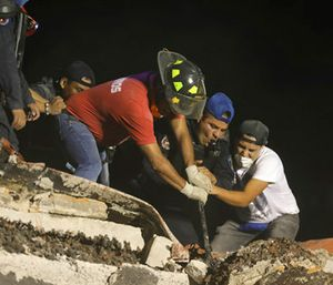 Rescue workers and volunteers search a building that collapsed after an earthquake, in the Colonia Obrera neighborhood of Mexico City. (AP Photo/Miguel Tovar)