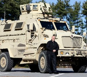 In this Wednesday, Nov. 13, 2013 photo, Warren County Undersheriff Shawn Lamouree poses in front the department's mine resistant ambush protected vehicle, or MRAP, in Queensbury, N.Y. (AP Photo/Mike Groll)