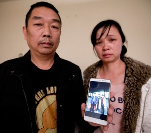Ronggao Zhang, left, and Lifeng Ye, display a photo them with their missing daughter, Yingying Zhang, in Urbana, Ill. (AP Photo/Michael Conroy File)