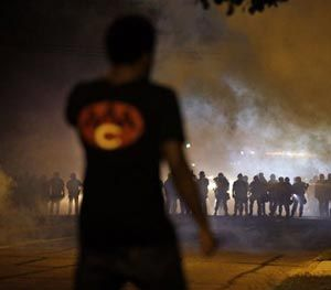 A man watches as police walk through a cloud of smoke during a clash with protesters Wednesday, Aug. 13, 2014, in Ferguson, Mo. (AP Image)