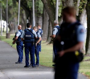 Police keep watch at a park across the road from a a mosque in central Christchurch, New Zealand, Friday, March 15, 2019. (AP Photo/Mark Baker)
