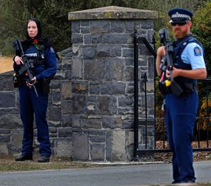 Police officer, left, stands guard with a rose on her chest to pay respect at the burial service for a victim of the Friday March 15 mosque shootings (AP Photo/Vincent Yu)