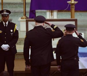 Two officers salute Chicago police Commander Paul Bauer before his funeral mass at Nativity of Our Lord Roman Catholic Church Saturday, Feb. 17, 2017, in Chicago. (John J. Kim/Chicago Tribune via AP)