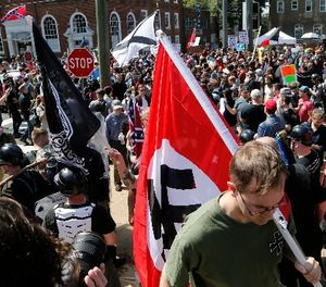 This Saturday, Aug. 12, 2017 image shows s white supremacist carrying a NAZI flag into the entrance to Emancipation Park in Charlottesville, Va. (AP Photo/Steve Helber)