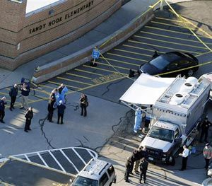 This Dec. 14, 2012 aerial file photo shows officials standing outside of Sandy Hook Elementary School in Newtown, Conn. (AP Image)