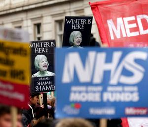 People wave banners depicting Britain's Prime Minister Theresa May, during a protest march in support of the National Health Service. (Photo/AP)