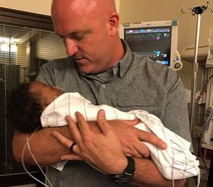 "Deputy Jeremie Nix cradles Kingston, the baby he rushed to the hospital. ""I was just in the right place at the right time,"" Nix said. (courtesy photo)"