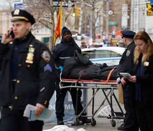 Police remove the body of a man following an incident in the Queens borough of New York. (AP Photo/Mark Lennihan)
