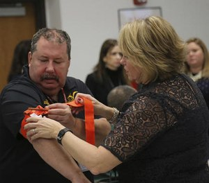 Two staffers from the Three Village Central School District in Stony Brook, N.Y., practice applying a tourniquet to one another during a first aid training session at Stony Brook University, Tuesday, Nov. 29, 2016, in New York. (AP Photo/Michael Balsamo)