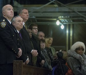 From left, NYPD's Chief of Department James O'Neill, NYPD Commissioner Bill Bratton, and New York City Mayor Bill de Blasio, attend mass at St. Patrick's Cathedral, Sunday, Dec. 21, 2014, in New York. (AP Image)