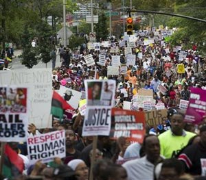 Demonstrators march to protest the death of Eric Garner, Saturday, Aug. 23, 2014, in the Staten Island borough of New York. (AP Image)