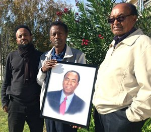 In this Dec. 5, 2015, file photo, family members of Isaac Amanios, from left, Robel Tekleab, Fessehatsion Gebreselassie and Abraham Amanios hold a portait of Isaac Amanios in Fontana, Calif. (AP Image)