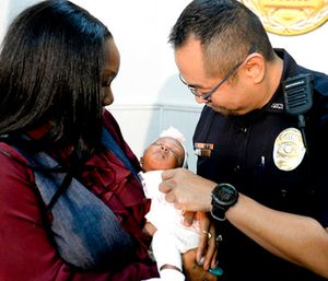 Savannah-Chatham police officer William Eng, right, plays with 29-day-old Bella Adkins while her mother, Tina Adkins, holds her. (Will Peebles/Savannah Morning News via AP)