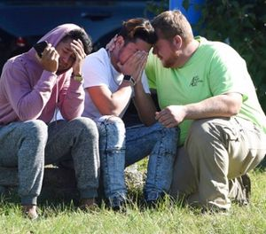 Workers from the Advanced Granite Solutions company console each other as police and Emergency Medical Services respond to a shooting at a business park in the Edgewood area of Harford County, Md., Wednesday, Oct. 18, 2017. (Matt Button/The Baltimore Sun via AP)