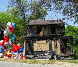 A balloon memorial sits outside the burnt home of a family that died in a fire in Akron, Ohio. (AP Photo/Dake Kang)