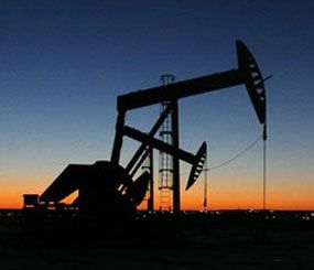 The lights of Williston, N.D. shine in the background of oil pumps on Tuesday, Feb. 25, 2014. (AP Image)