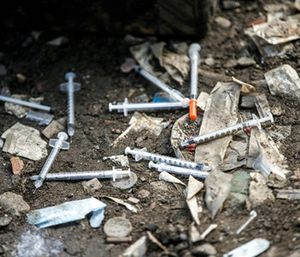 Used needles litter the ground at an open air drug market along Conrail train tracks in the Kensington section of Philadelphia. (Michael Bryant /The Philadelphia Inquirer via AP