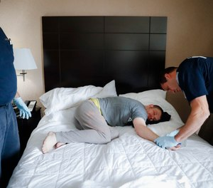 In this Nov. 2, 2017, file photo, Cincinnati police officers, firefighters and medics respond to a possible overdose report at a hotel in downtown Cincinnati. (AP Photo/John Minchillo, File)