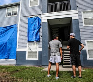 Residents at Westbrook Apartments get a first look at their building where a gunman held four children hostage before taking their life and his own, Tuesday, June 12, 2018, in Orlando, Fla. (Jacob Langston/Orlando Sentinel via AP)