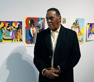 Richard Phillips stands next to some of his artwork during an interview at the Community Art Gallery in Ferndale, Mich. Phillips was exonerated of murder in 2018 after 45 years in prison. Lawyers say he should be entitled to more than $2 million under Michigan's wrongful conviction law, but the state so far is resisting. So Phillips, 73, is selling some of his 400-plus watercolors that he painted in prison. (AP Photo/Carlos Osorio)