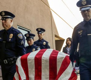 """Palm Springs police officers carry the casket of officer Jose """"Gil"""" Vegaat Palm Springs Convention Center on Oct. 18. (Photo/Los Angeles Times)"""
