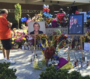 """A visitor pays his respect at a memorial for Palm Springs Police Officers Lesley Zerebny, and Jose """"Gil"""" Gilbert Vega,seen in photos placed in front of the police station in Palm Springs, Calif., on Monday, Oct. 10, 2016. (AP Photo/Amy Taxin)"""