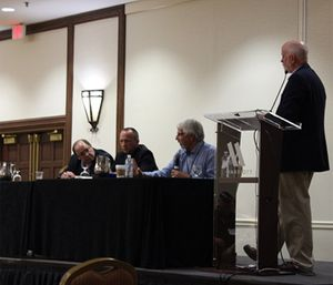 Panelists Jay Bradshaw (standing), Joe Schmider, Andy Gienapp and Tom Nehring discuss challenges facing rural EMS.