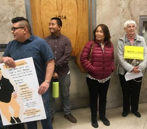 "In this Oct. 24, 2018, file photo, Andrew Medina, left, holds a sign during a rally backing a pardon for Borey Ai, who also goes by ""PJ"" or ""Peejay,"" in Sacramento, Calif. (AP Photo/Don Thompson, File)"