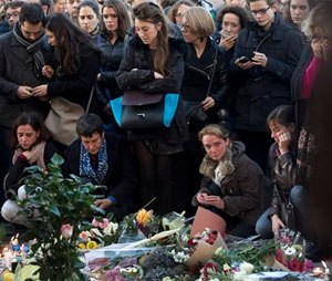 People pay their respect to the victims at the site of the attacks on restaurant Le Petit Cambodge (Little Cambodia) and the Carillon Hotel on the first of three days of national mourning in Paris. (AP Photo/Peter Dejong)