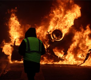A demonstrator watches a burning car near the Champs-Elysees avenue during a demonstration Saturday, Dec.1, 2018 in Paris. (AP Photo/Kamil Zihnioglu)