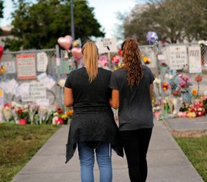 In this Feb. 19, 2018, file photo Sara Smith, left, and her daughter Karina Smith visit a makeshift memorial outside the Marjory Stoneman Douglas High School, where 17 students and faculty were killed in a mass shooting in Parkland, Fla.  (AP Photo/Gerald Herbert, File )