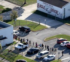 Students are evacuated by police out of Stoneman Douglas High School in Parkland, Fla., after a shooting on Feb. 14, 2018. According to testimony, the death toll was higher because a security recommendation was ignored. (Mike Stocker/Sun Sentinel/TNS)