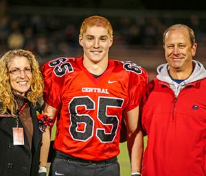 """Timothy Piazza, center, with his parents Evelyn Piazza, left, and James Piazza, right, during Hunterdon Central Regional High School football's """"Senior Night"""" at the high school's stadium in Flemington, N.J. (Patrick Carns via AP)"""