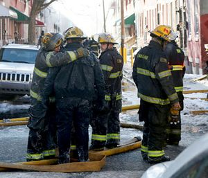 Firefighters embrace as their colleagues battle a row home fire in Philadelphia. (Tim Tai/The Philadelphia Inquirer via AP)