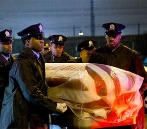 The remains of Philadelphia Police Officer Robert Wilson III are transferred to a horse drawn hearse during a winter rainstorm on Saturday. (AP Image)