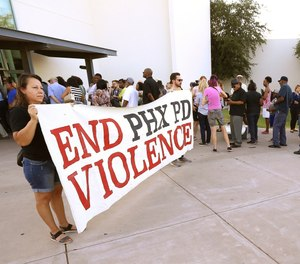 In this June 18, 2019, file photo, people line up near protesters outside a venue for a community meeting in Phoenix. (AP Photo/Ross D. Franklin, File)
