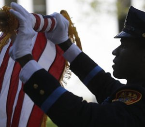 An officer rolls up a flag during a ceremony at the New York State Police Officers' Memorial on Tuesday, May 10, 2016, in Albany, N.Y. (AP Image)