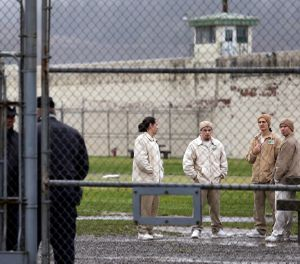 In this file photo, inmates mingle in a recreation yard in view of guards, left, at the Monroe Correctional Complex in Monroe, Wash. (AP Photo/Elaine Thompson, File)