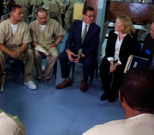 Connecticut Gov. Dannel P. Malloy, first lady Cathy Malloy and Correction Department Commissioner Scott Semple speak with inmates inside the Cheshire Correctional Institution in Cheshire, Conn. on Wednesday May 30, 2018. (AP Photo/Pat Eaton-Robb)
